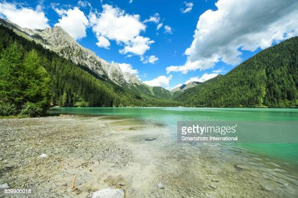 antholzer see (lago di anterselva) with turquoise waters and dramatic sky, south tyrol, italy - lakeshore stock pictures, royalty-free photos & images