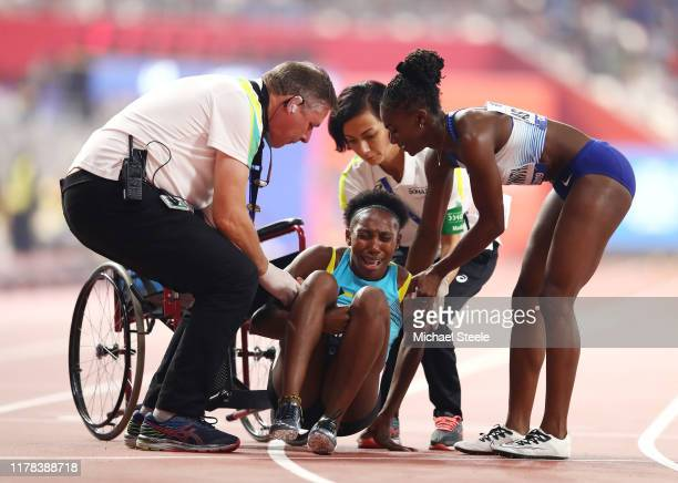 Anthonique Strachan of the Bahamas is assisted by Dina AsherSmith of Great Britain and officials after the Women's 200 metres semi finals during day...