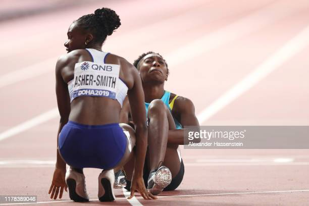 Anthonique Strachan of the Bahamas is assisted by Dina AsherSmith of Great Britain after the Women's 200 metres semi finals during day five of 17th...