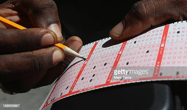 Anthony Adams fills out his numbers while waiting to purchase Powerball tickets in Manhattan on May 17 2013 in New York City The Powerball lottery...