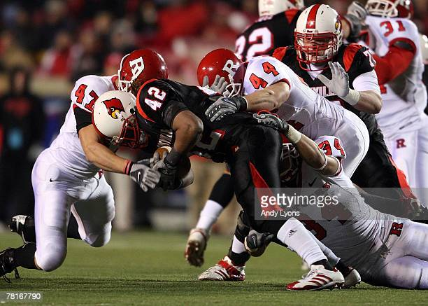 Anthony Allen of the Louisville Cardinals is tackled by Brandon Renkart Ryan D'Imperio and Kevin Malast of the Rutgers Scarlet Knights during the Big...