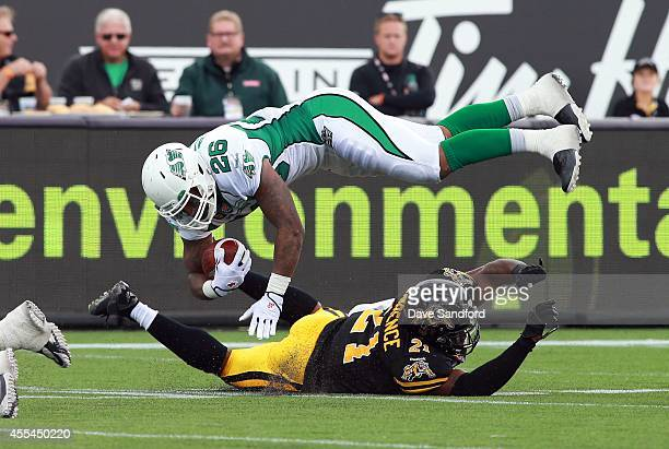 Anthony Allen of the Saskatchewan Roughriders is tackled by Simoni Lawrence of the Hamilton TigerCats during their game at Tim Hortons Field on...