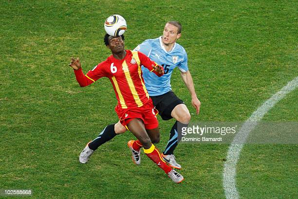 Anthony Annan of Ghana and Diego Perez of Uruguay challenge for the ball during the 2010 FIFA World Cup South Africa Quarter Final match between...