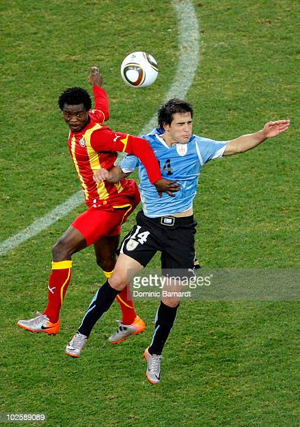 Anthony Annan of Ghana and Nicolas Lodeiro of Uruguay battle for a high ball during the 2010 FIFA World Cup South Africa Quarter Final match between...
