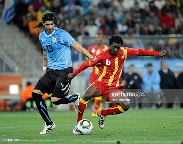 Anthony Annan of Ghana challenged by Sebastian Abreu of Uruguay during the 2010 FIFA World Cup South Africa Quarter Final match between Uruguay and...