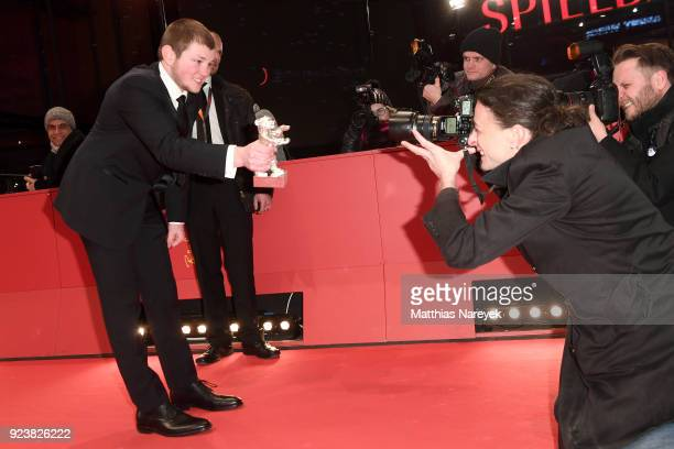 Anthony Bajon winner of the Silver Bear for Best Actor for 'The Prayer' poses with his award for the photographers on the red carpet after the...