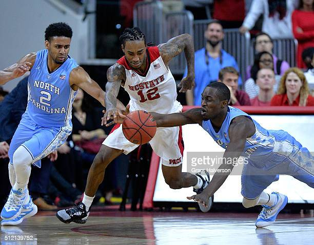 Anthony Barber of the North Carolina State Wolfpack battles Joel Berry II and Theo Pinson of the North Carolina Tar Heels for a loose ball during...