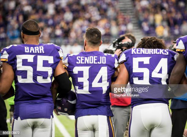 Anthony Barr, Andrew Sendejo, and Eric Kendricks of the Minnesota Vikings join their teammates in linking arms before the game against the Detroit...