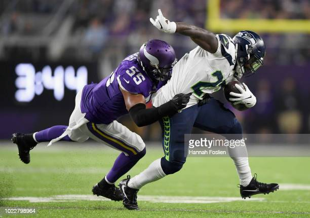 Anthony Barr of the Minnesota Vikings tackles Mike Davis of the Seattle Seahawks during the second quarter in the preseason game on August 24 2018 at...