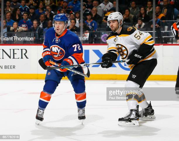 Anthony Beauvillier of the New York Islanders and Adam McQuaid of the Boston Bruins battle for position in front of the net during the first period...