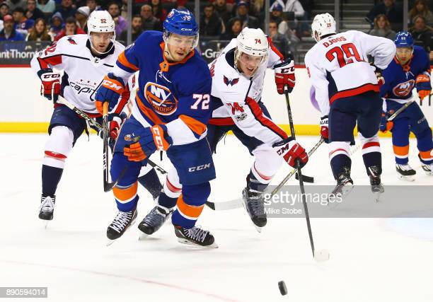 Anthony Beauvillier of the New York Islanders and John Carlson of the Washington Capitals chase down a loose puck during the first period at Barclays...