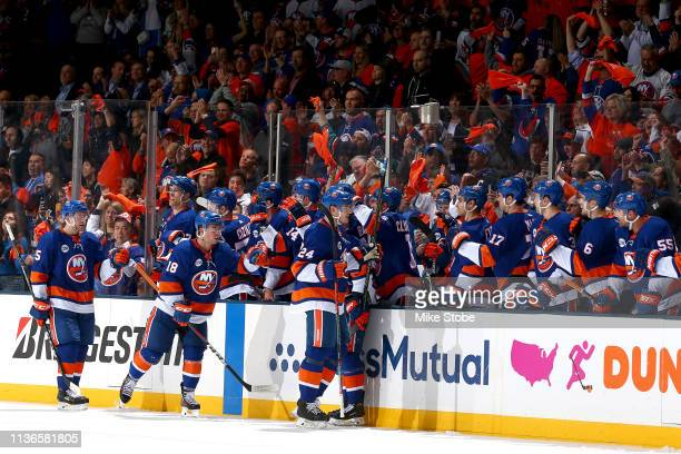 Anthony Beauvillier of the New York Islanders is congratulated by his teammates after scoring a second period goal against the Pittsburgh Penguins in...