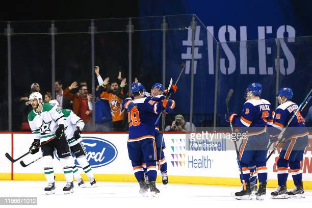Anthony Beauvillier of the New York Islanders is congratulated by his teammates after scoring the game winning goal against the Dallas Stars during...