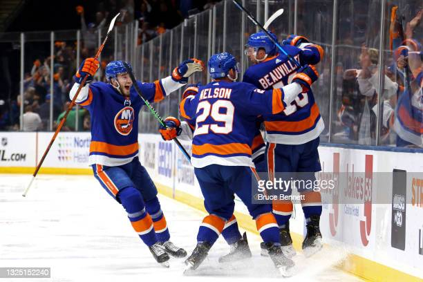 Anthony Beauvillier of the New York Islanders is congratulated by Brock Nelson and Noah Dobson after scoring the game-winning goal during the first...