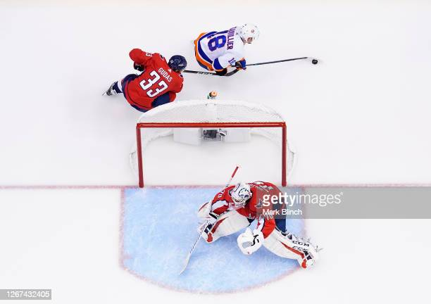 Anthony Beauvillier of the New York Islanders skates around the Capitals net as Radko Gudas of the Washington Capitals gives chase in the third...