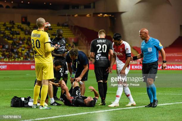 Anthony Briancon of Nimes with teammates Radamel Falcao of Monaco and referee Amaury Delerue during the Ligue 1 match between AS Monaco and Nimes at...