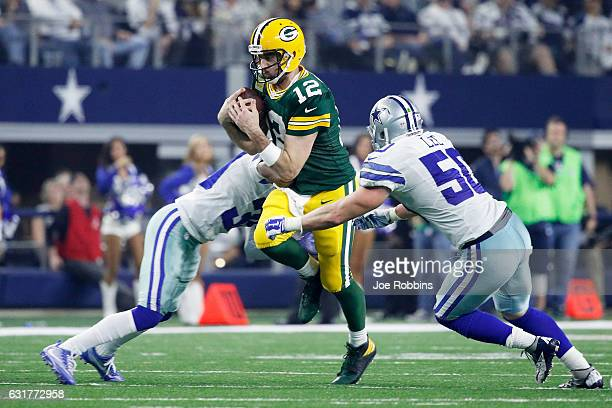 Anthony Brown and Sean Lee of the Dallas Cowboys tackle Aaron Rodgers of the Green Bay Packers in the second half during the NFC Divisional Playoff...