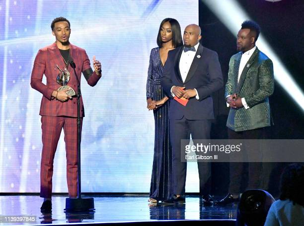 Anthony Brown and VaShawn Mitchell stand onstage as Jonathan McReynolds winner of the Male Vocalist of the Year award speaks during the 34th annual...