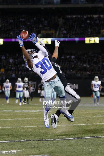 Anthony Brown of the Dallas Cowboys is unable to make an interception against Michael Crabtree of the Oakland Raiders at OaklandAlameda County...