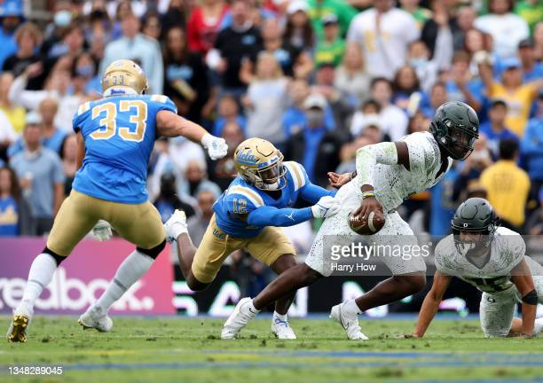 Anthony Brown of the Oregon Ducks escapes from Martell Irby and Bo Calvert of the UCLA Bruins during the first half at Rose Bowl on October 23, 2021...