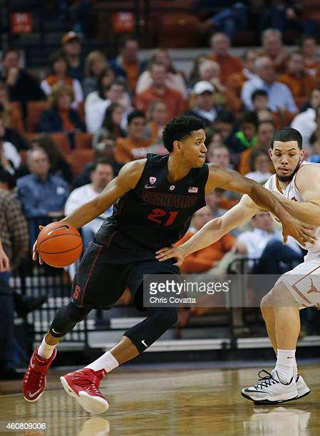 Anthony Brown of the Stanford Cardinal drives around Javan Felix of the Texas Longhorns at the Frank Erwin Center on December 23 2014 in Austin Texas