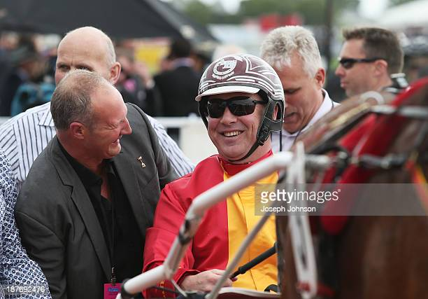 Anthony Butt driver of Sundown In Paris is congratulated by an owner after winning the Cromwell Lake Dunstan Handicap Trot race during New Zealand...