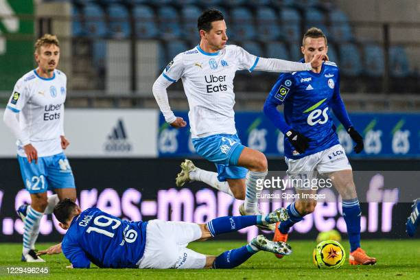 Anthony Caci of Racing Strasbourg trips up with Florian Thauvin of Olympique de Marseille during the Ligue 1 match between RC Strasbourg and...