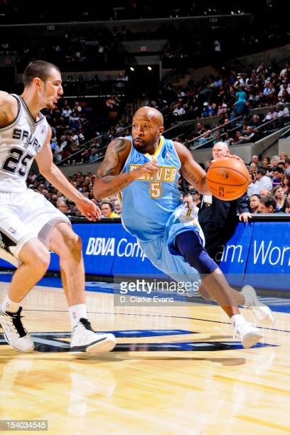 Anthony Carter of the Denver Nuggets drives against Nando de Colo of the San Antonio Spurs during a preseason game on October 12 2012 at the ATT...