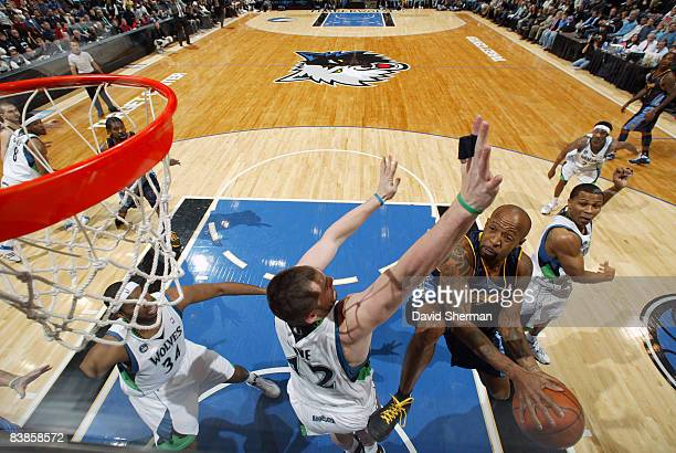 Anthony Carter of the Denver Nuggets goes in for a layup against Kevin Love of the Minnesota Timberwolves during the game on November 29 2008 at the...