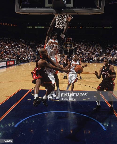 Anthony Carter of the Miami Heat passes to Rasual Butler around Jason Richardson of the Golden State Warriors during the NBA game at The Arena in...