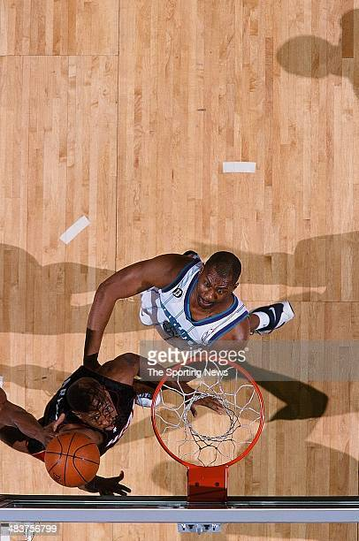 Anthony Carter of the Miami Heat puts a shot up over Elden Campbell of the Charlotte Hornets during the game on April 19 2000 at Charlotte Coliseum...