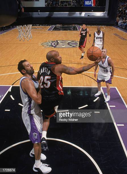 Anthony Carter of the Miami Heat shoots a reverse layup over Vlade Divac of the Sacramento Kings during the NBA game at Arco Arena on January 5 2003...