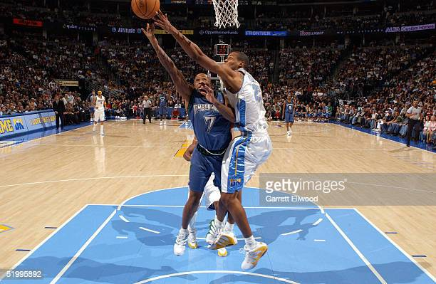 Anthony Carter of the Minnesota Timberwolves is blocked by Marcus Camby of the Denver Nuggets on January 14 2005 at Pepsi Center in Denver Colorado...