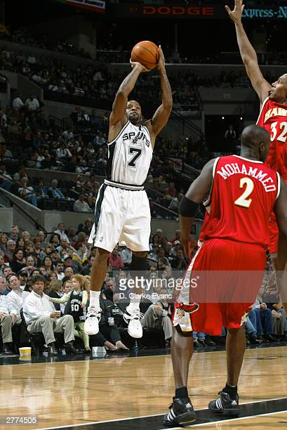 Anthony Carter of the San Antonio Spurs shoots over Nazr Mohammed and Boris Diaw of the Atlanta Hawks during the game at the SBC Center on November...