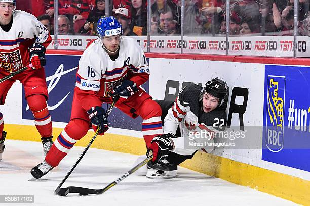 Anthony Cirelli of Team Canada tries to play the puck as he falls against Michael Spacek of Team Czech Republic during the 2017 IIHF World Junior...