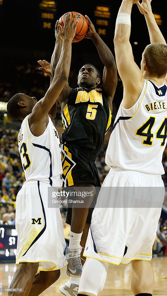 Anthony Clemmons #5 of the Iowa Hawkeyes tries to get a second half shot off between Caris LeVert #23 and Max Bielfeldt #44 of the Michigan Wolverines at Crisler Center on January 6, 2013 in Ann Arbor, Michigan. Michigan won the game 95-67.
