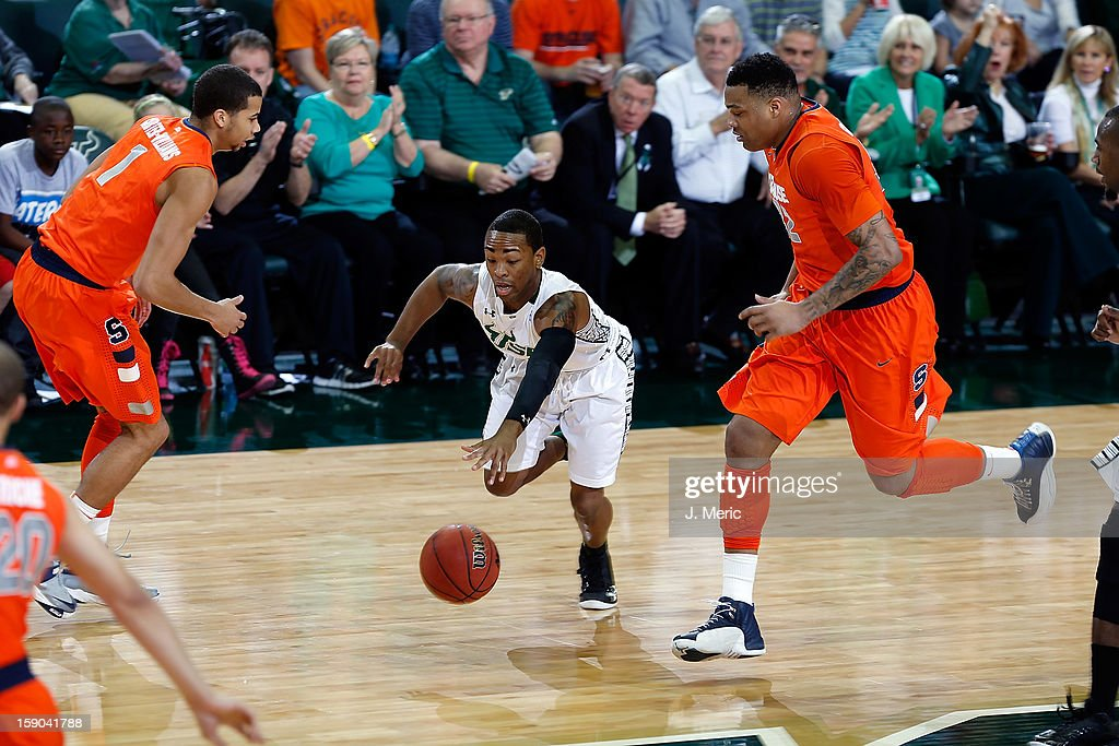 Anthony Collins #11 of the South Florida Bulls dribbles between defenders DaJuan Coleman #32 and Michael Carter-Williams #1 of the Syracuse Orange during the game at the Sun Dome on January 6, 2013 in Tampa, Florida.