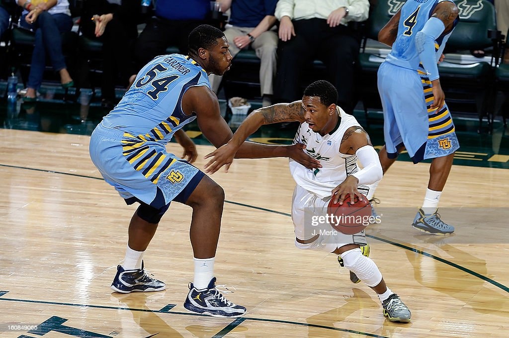 Anthony Collins #11 of the South Florida Bulls drives around Davante Gardner #54 of the Marquette Golden Eagles during the game at the Sun Dome on February 6, 2013 in Tampa, Florida.