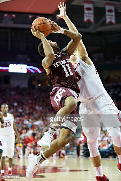 Anthony Collins of the Texas AM Aggies goes up for a shot against Dusty Hannahs of the Arkansas Razorbacks at Bud Walton Arena on January 27 2016 in...