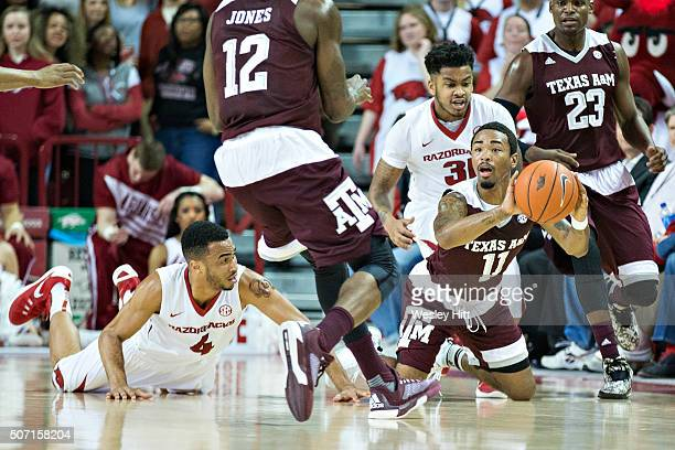 Anthony Collins of the Texas AM Aggies makes a pass from his knees after diving to the floor for a loose ball during the second half of a game...