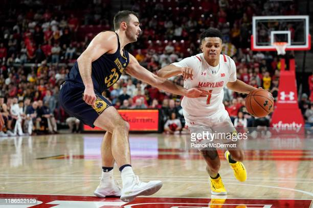 Anthony Cowan Jr #1 of the Maryland Terrapins dribbles as John Mooney of the Notre Dame Fighting Irish defends in the second half at Xfinity Center...