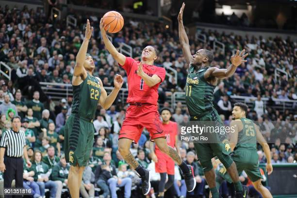 Anthony Cowan Jr #1 of the Maryland Terrapins drives to the basket defended by Miles Bridges and Lourawls Nairn Jr #11 of the Michigan State Spartans...
