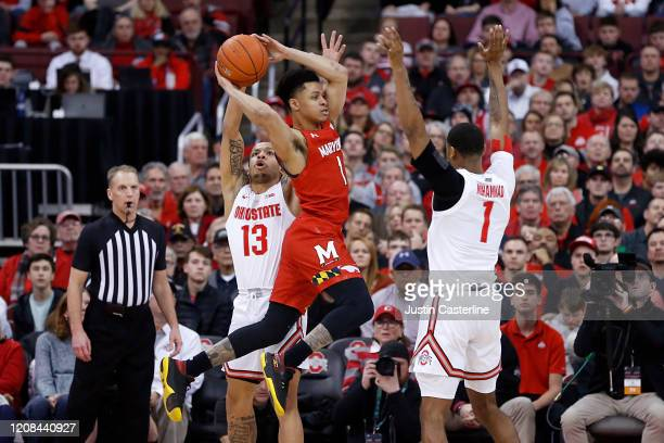 Anthony Cowan Jr #1 of the Maryland Terrapins passes the ball in while being guarded by CJ Walker and Luther Muhammad of the Ohio State Buckeyes at...