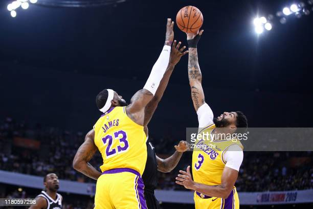 Anthony Davis and LeBron James of the Los Angeles Lakers block against DeAndre Jordan of the Brooklyn Nets during a preseason game as part of 2019...