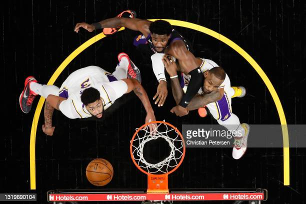 Anthony Davis and LeBron James of the Los Angeles Lakers block out Deandre Ayton of the Phoenix Suns during the first half of Game One of the Western...