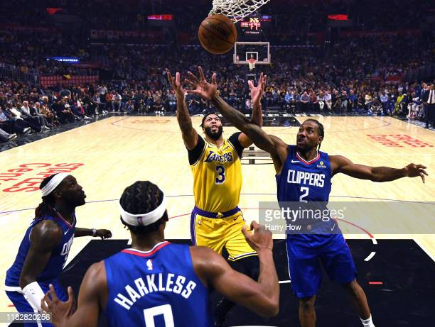 Anthony Davis of the Los Angeles Lakers and Kawhi Leonard of the LA Clippers reach for a rebound with Montrezl Harrell and Maurice Harkless during a...