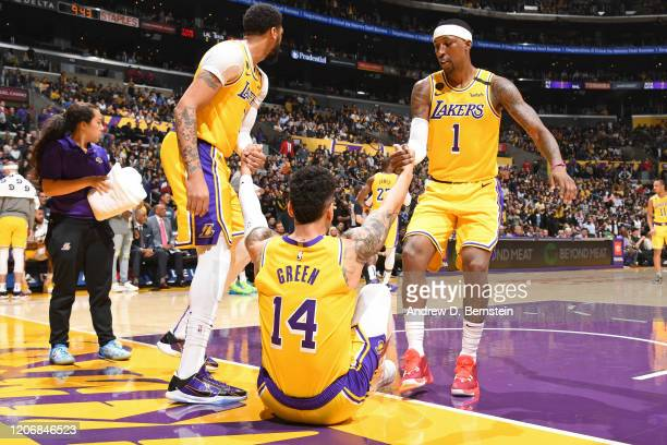 Anthony Davis of the Los Angeles Lakers and Kentavious CaldwellPope of the Los Angeles Lakers helps up Danny Green of the Los Angeles Lakers during...