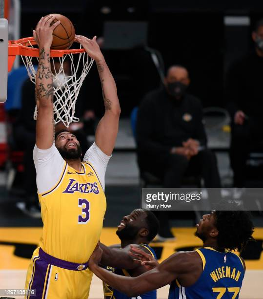 Anthony Davis of the Los Angeles Lakers dunks in front of Draymond Green and James Wiseman of the Golden State Warriors during the first half at...