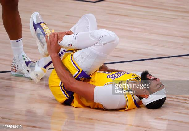 Anthony Davis of the Los Angeles Lakers goes down holding his ankle after taking a shot during the fourth quarter against the Denver Nuggets in Game...