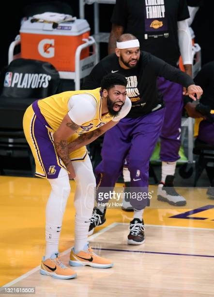 Anthony Davis of the Los Angeles Lakers grimaces next to Jared Dudley before leaving the game against the Phoenix Suns in the first quarter during...